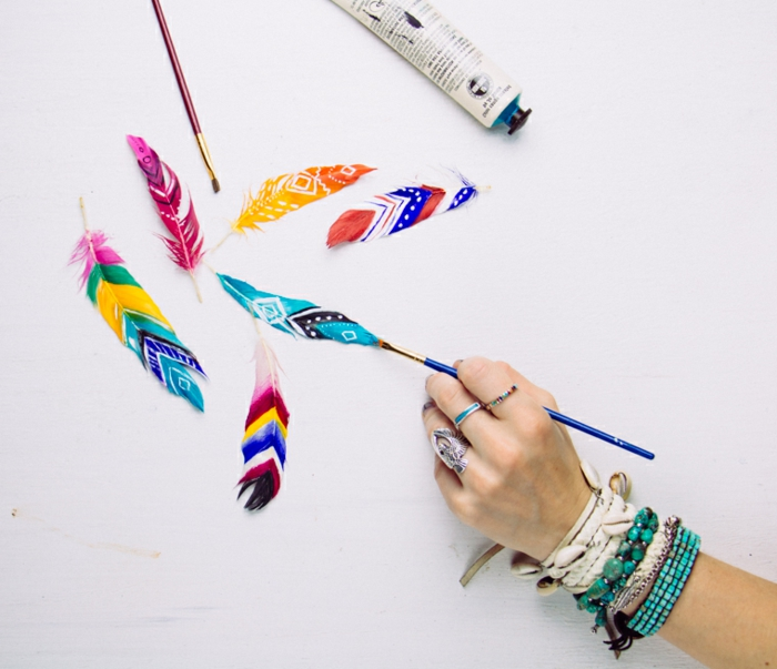 feathers painted in different colors, and decorated with patterns, homemade crafts, hand with many bracelets and rings, holding a blue brush