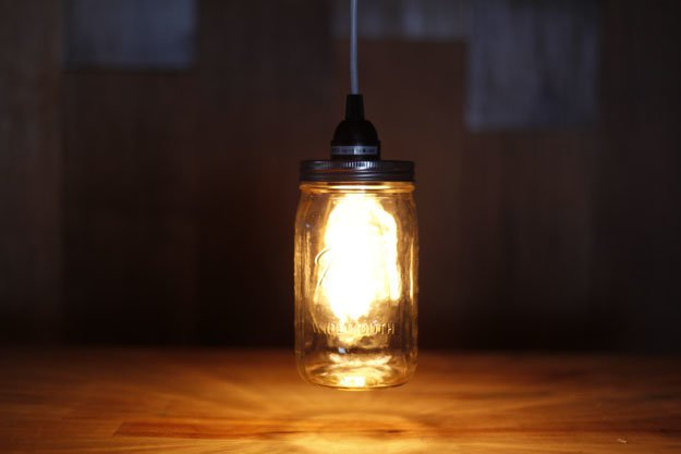 lit lamp, made from shining lighbulb, inside a clear mason jar, hanging from black cable
