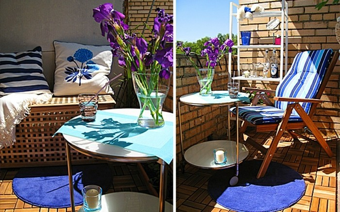 brick walls and wooden floor, wooden settee with two cushions, bright blue round rug, and round table with clear vase, containing purple flowers