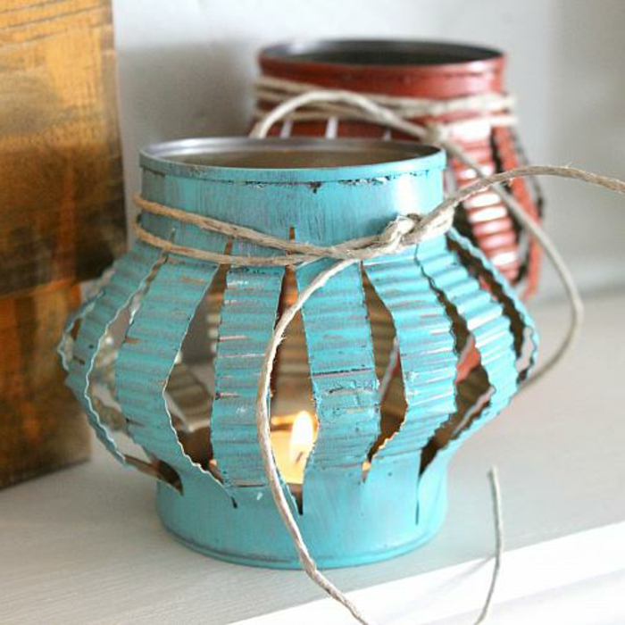 lanterns made from old tin cans, cut and pressed, diy craft projects, tied with thread, and containing small lit candles