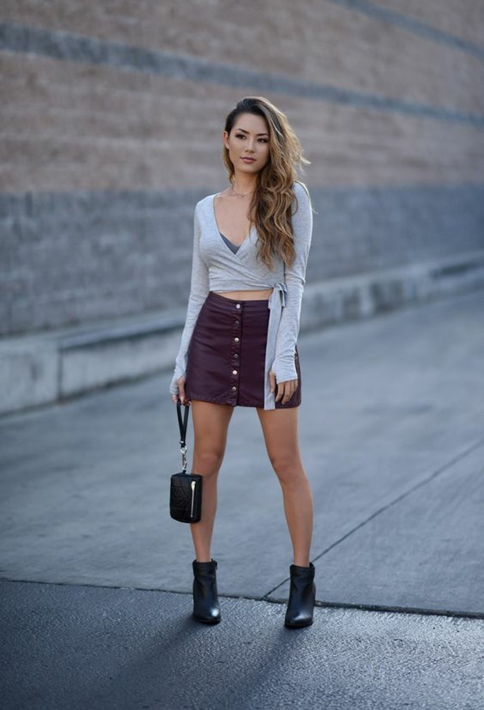 casual dress code, pale grey long sleeved top, purple leather button up skirt, and black ankle boots, worn by woman with blonde wavy hair