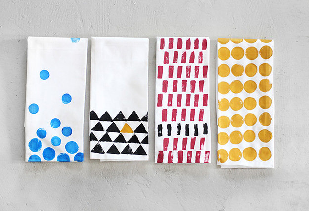 folded white napkins, a total of four, each decorated with a different stamped pattern, blue dots, black and yellow triangles, red and black rectangles, large yellow dots