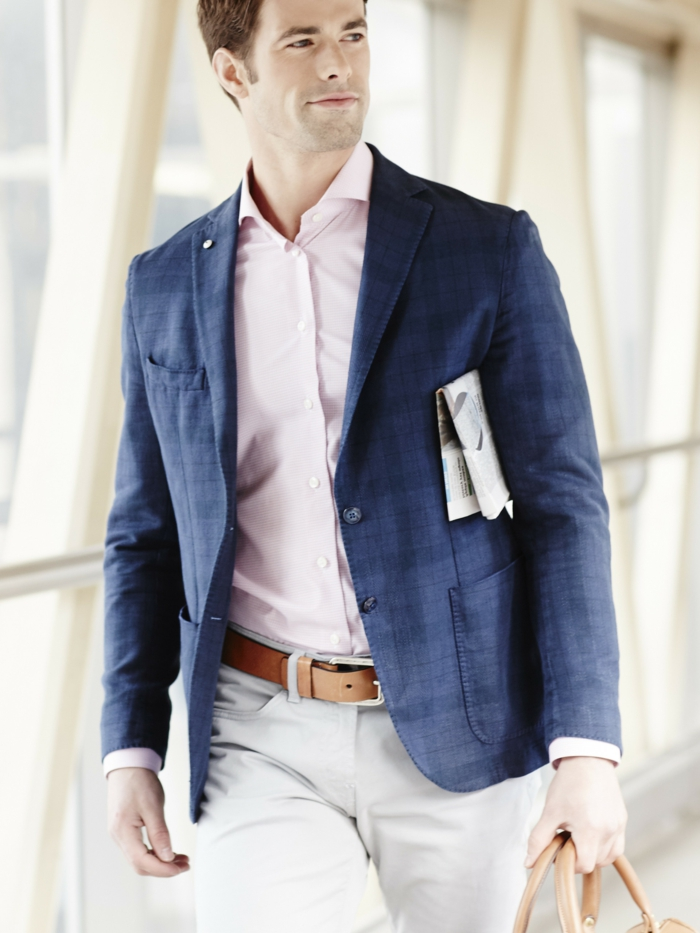 travelling businessman, wearing blue patterned blazer, pale pink shirt, and white pants with brown leather belt, business casual outfits