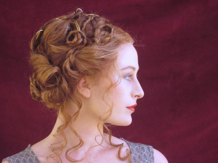 unusual hairstyle for ginger hair, made up of curls, twists and braids, worn by woman with red lipstick, looking to one side