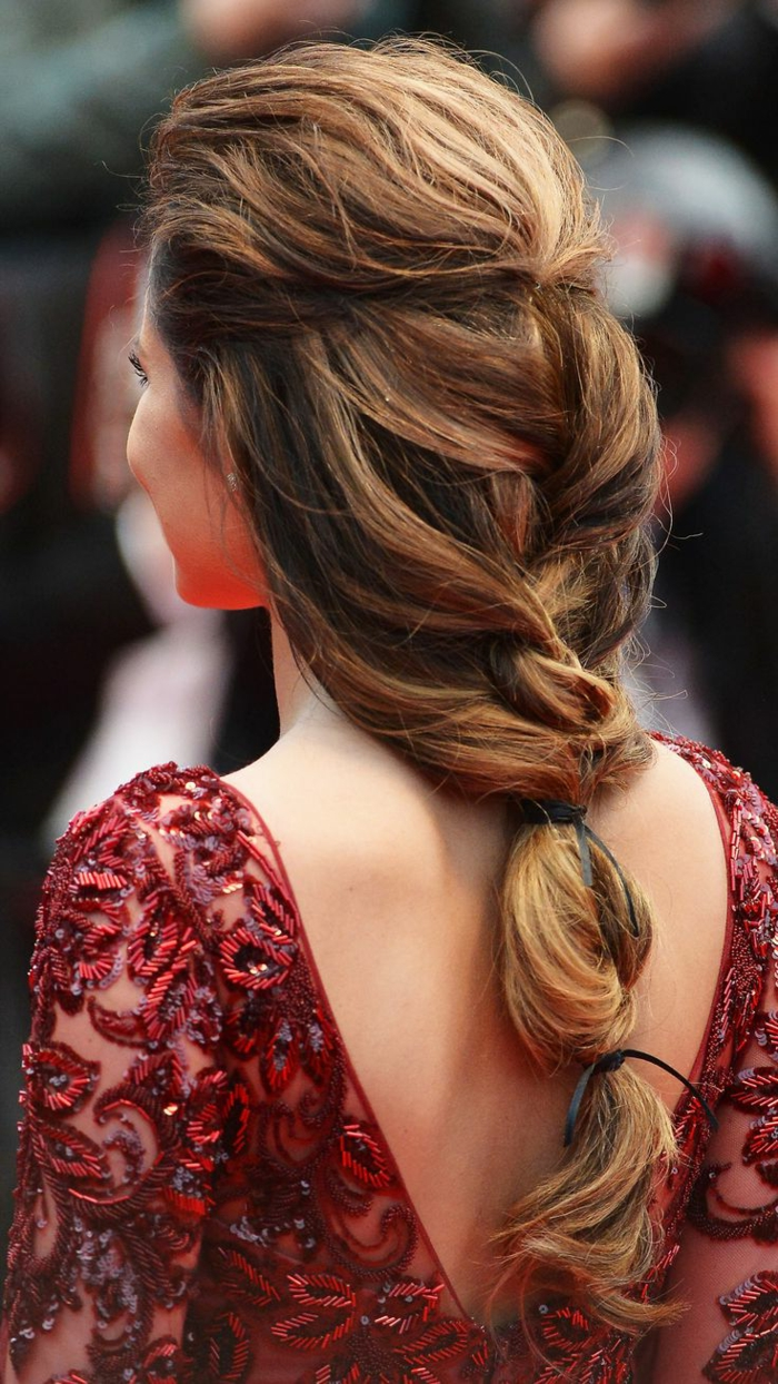 renaissance braids, dark honey blond hair, woven in a messy braid, tied with black ribbons, worn by slim woman, in red open-back embroidered dress