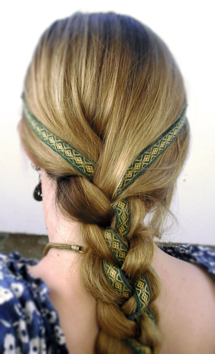 elizabethan hairstyles, blonde hair woven in a simple braid, with a green and gold-embroidered ribbon running through it