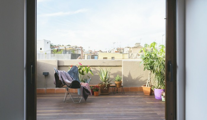 large minimalist terrace, with a single lounging chair, covered by several blankets, few different potted plants in pink, orange and green pots nearby