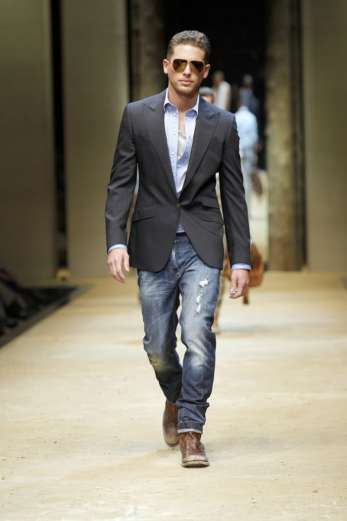 business casual dress code, male catwalk model, with distressed jeans, pale blue shirt, and black blazer, wearing sunglasses and worn, brown leather shoes