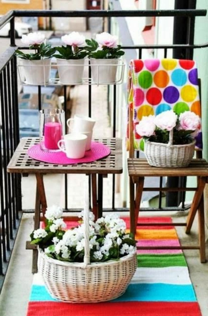 small square wooden table, near wooden chair, porch ideas, several potted plants in pots and baskets, bright table decorations, and multicolored blanket