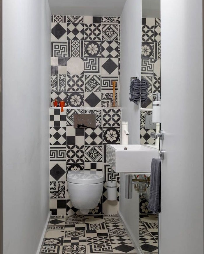 bathroom remodels, narrow toilet with two white walls, third wall and floor are covered in black and white, mismatched and patterned tiles, rectangular white sink and plain toilet bowl