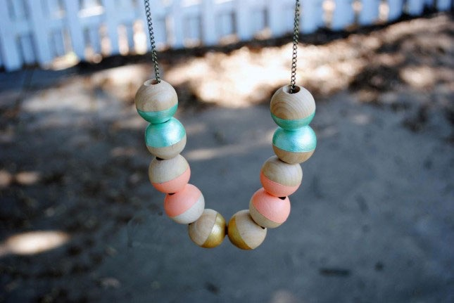several wooden beads, half colored in turquoise, coral pink or gold, stringed on a chain