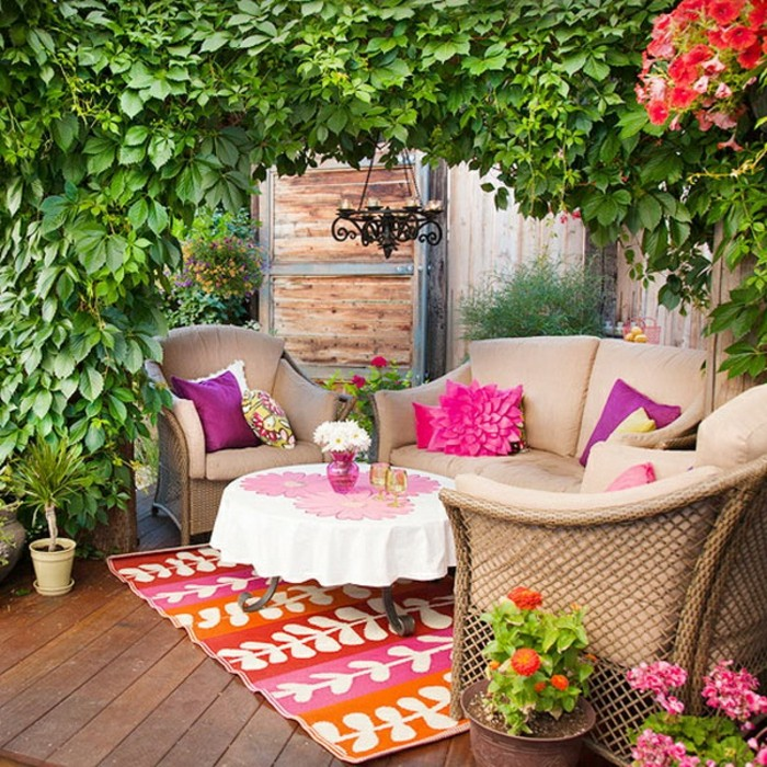pale beige garden furniture, couch and two comfy seats, small round table, multicolored rug and potted plants, outdoor patio ideas, lots of greenery