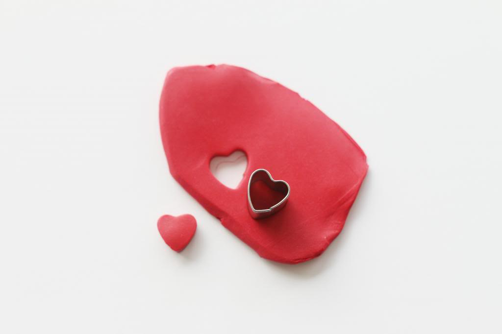 modelling clay in red, with a heart-shapped cutter, small heart-shaped hole, art and craft ideas, red clay heart shape nearby