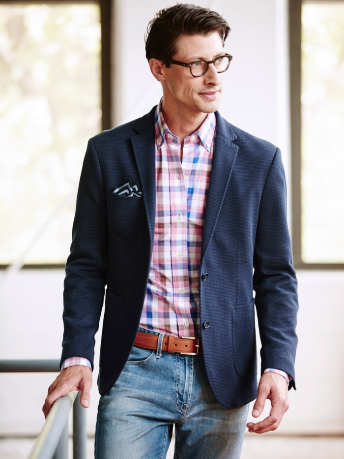 working professional with glasses, wearing plaid shirt, navy blazer with pocket handkerchief, and pale business casual jeans, with brown leather belt