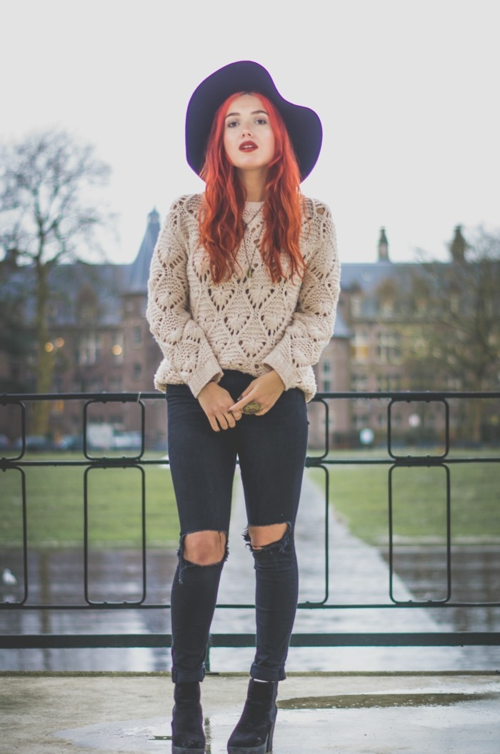 cute work outfits, young woman with long wavy red hair, wearing chinky knit pale beige jumper, and black torn skinny trousers, with dark ankle boots, and big felt hat