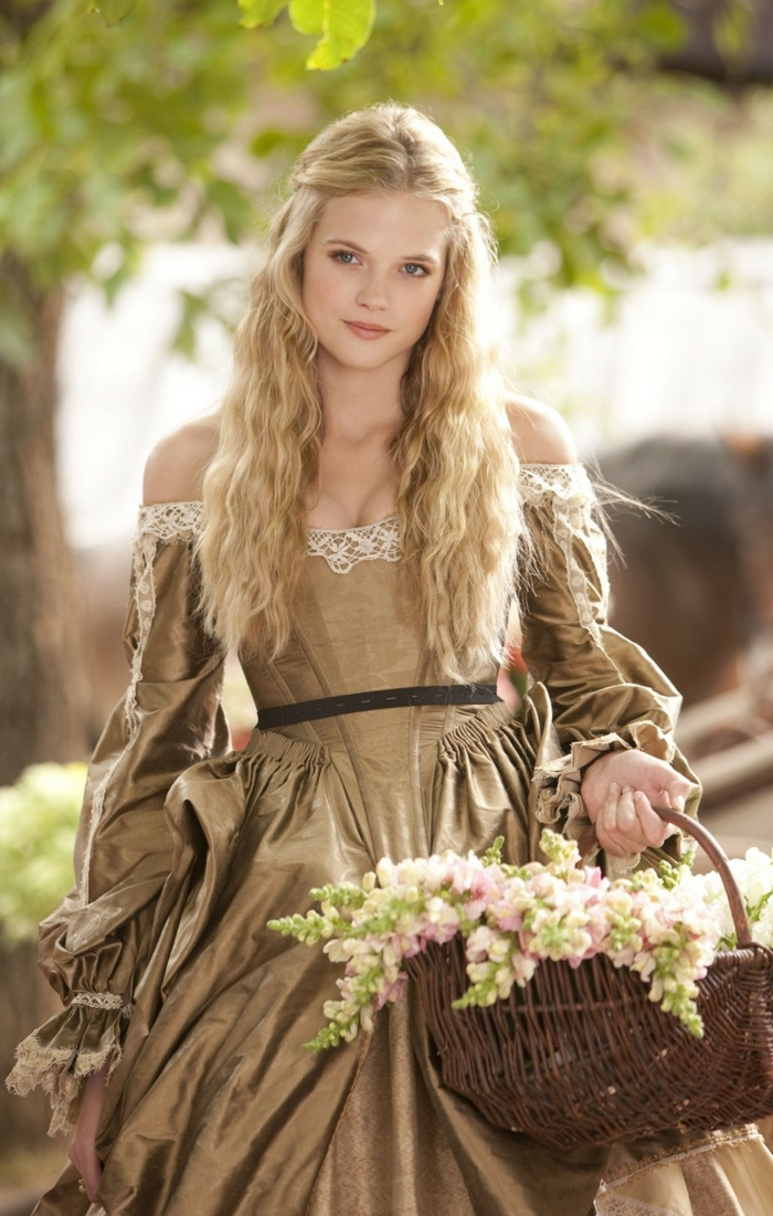 renaissance hairstyles, smiling girl with long, wavy blonde hair, partially tied back, wearing pale brown renaissance dress, and carrying a basket with flowers