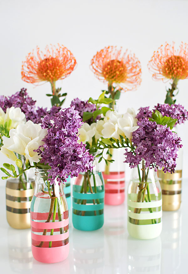 art and craft ideas, seven clear vases, partially painted with gold and pink, blue and white stripes, containing lilac stalks, white and orange flowers
