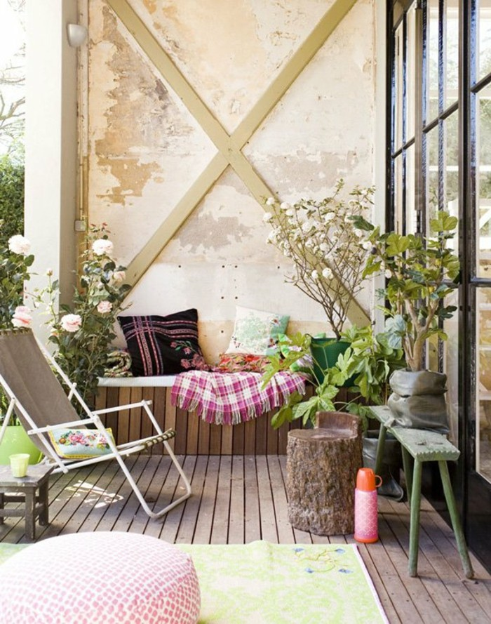 shabby chic wall with beams, wooden settee with blanket and pillows, outdoor patio ideas, green bench and lounging chair, tree stump and potted plants