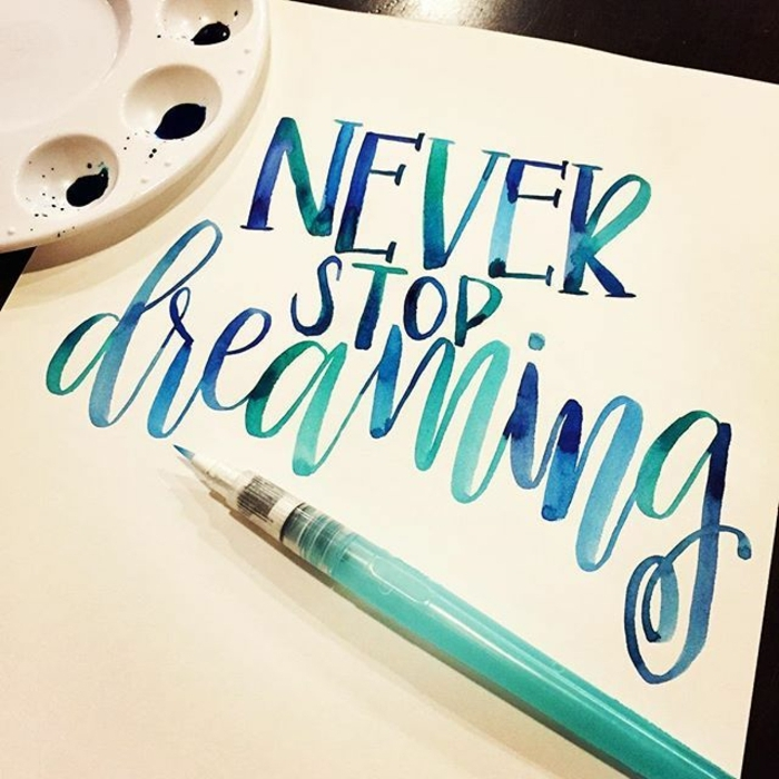 white sheet of paper, with the words never stop dreaming, written in blue watercolor, palette with blue paint, and marker-like brush nearby, homemade crafts