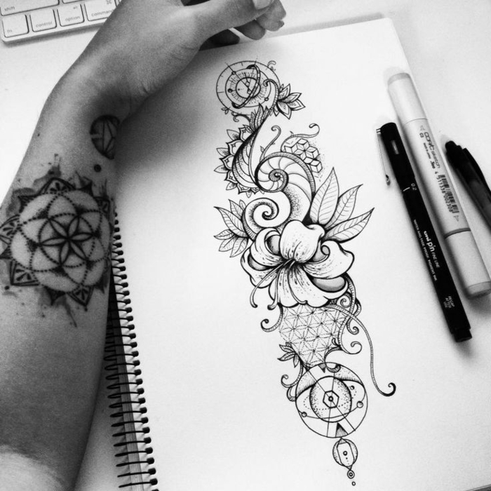 flower tattoo designs, male hand with mandala tattoo, leaning against a sketchbook, containing an ink drawing of a hibiscus flower, decorated with swirls and geometric patterns, fineliner pencil and marker nearby