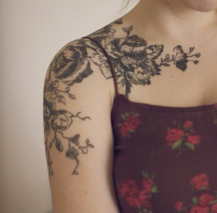 shoulder flower tattoos, woman in purple strappy top, with elaborate floral shoulder tattoo, made in black ink, going down her arm, and across her collar bone