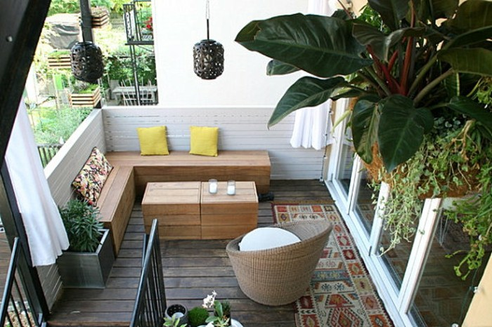 solid wooden corner settee, with three pillows and matching table, multicolored rug and round chair nearby, covered patio ideas, hanging lights and various potted plants