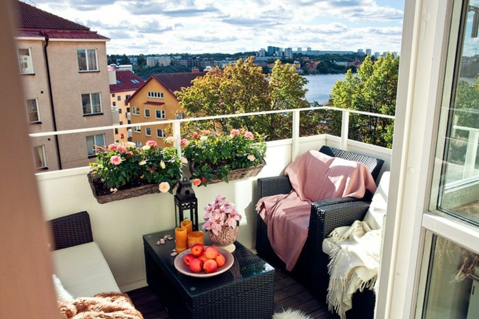 porch décor, black table with candles, fruit and flowers, near black cozy chairs, with white and pink blankets, near potted plants, lovely town view