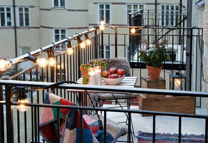 veranda with black railing, covered in a string of shining lightbulbs, small square wooden table with matching chairs, front porch decorating ideas, decorative wooden crates and potted plant
