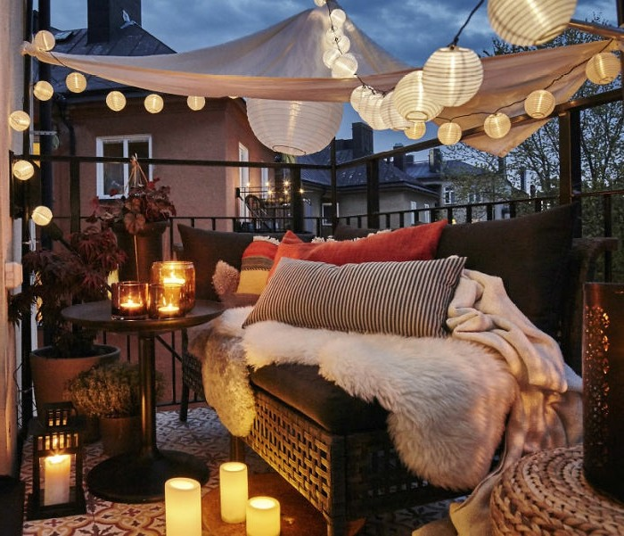 brown settee with pillows, throws and blankets, near small round black table, with many lit candles, covered patio ideas, baldachin with many lit lanterns overhead
