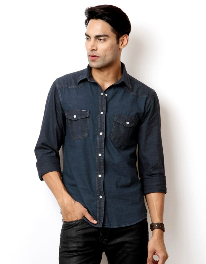 business casual attire, dark denim shirt with rolled sleeves, on black-haired man, wearing smooth and shiny black trousers