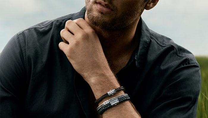 plain black casual shirt, on man with stubble, wearing three woven metal bracelets