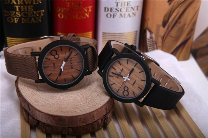 wooden detail wristwatches, one with a brown strap, and one with a black strap, placed on wooden stands, near several books