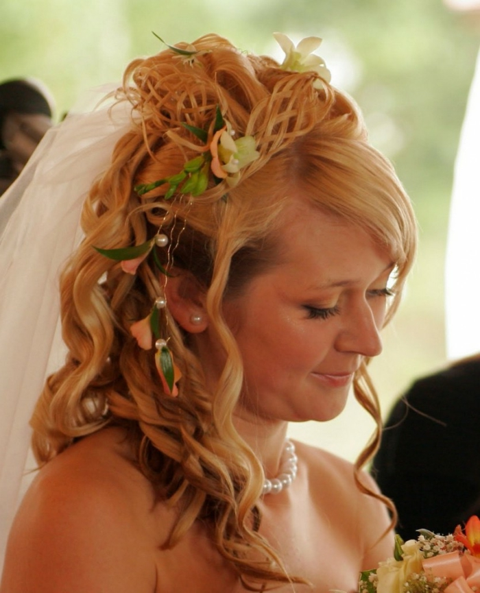 middle age hairstyles, smiling bride with white veil, blonde hair falling in lose curls, with a tiara made from twisted hair strands, decorated with pearls, pink and white flowers