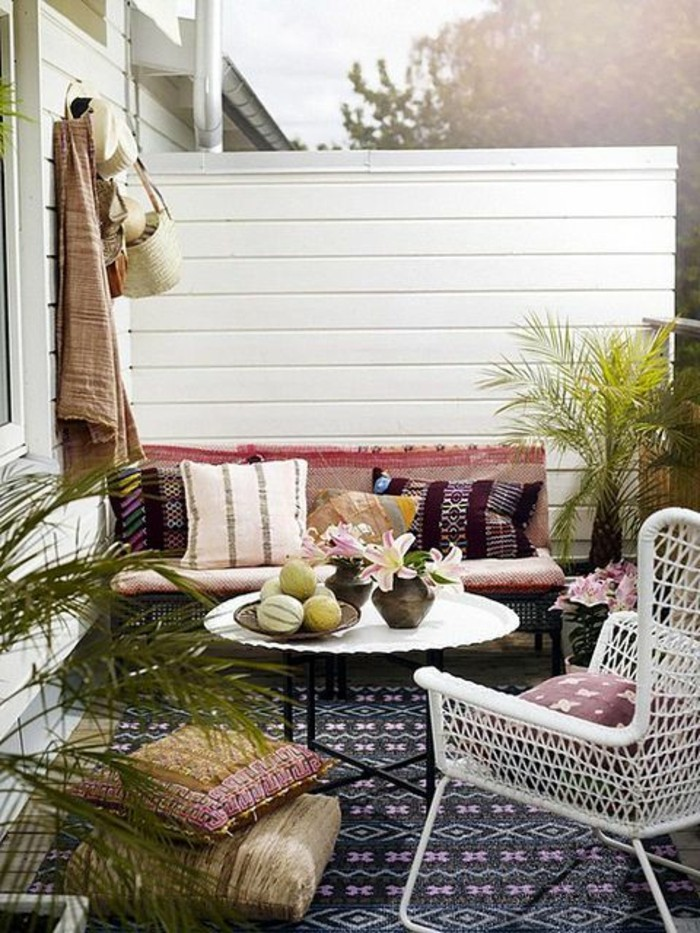settee with four multicolored cushions, near white round table, and white chair, front porch décor, with patterned rug and potted plants