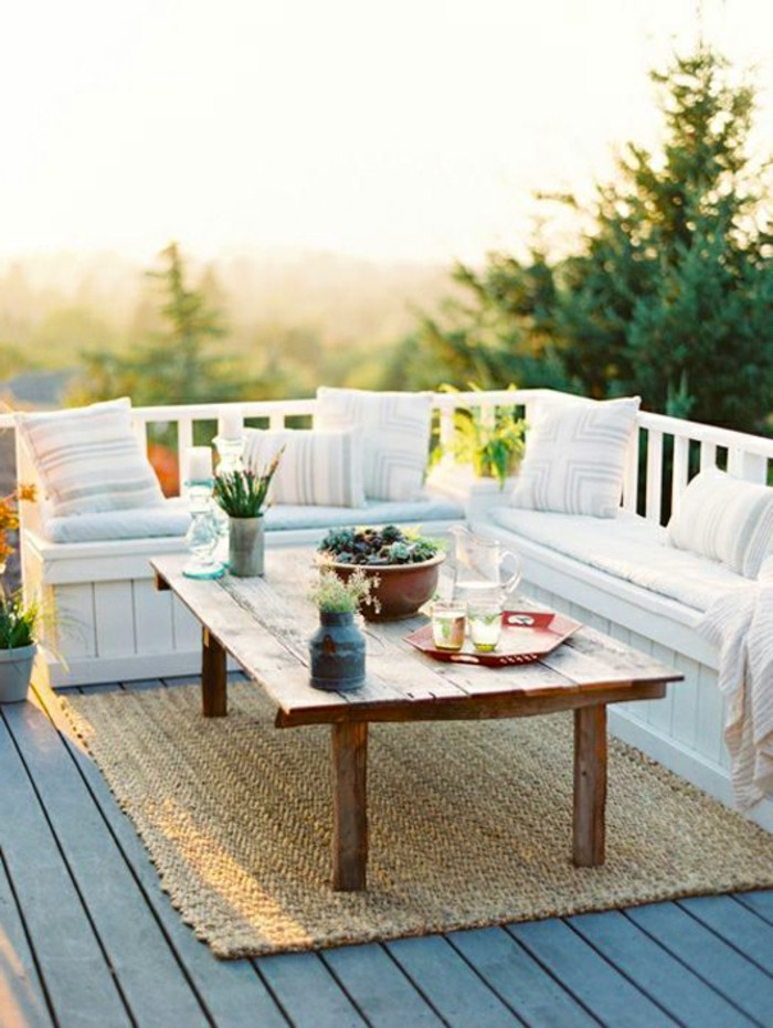 massive wooden table, with vases and a trey with glasses and pitcher, white wooden corner settee, with pale pillows and blankets, beige coarse rug, outdoor patio ideas