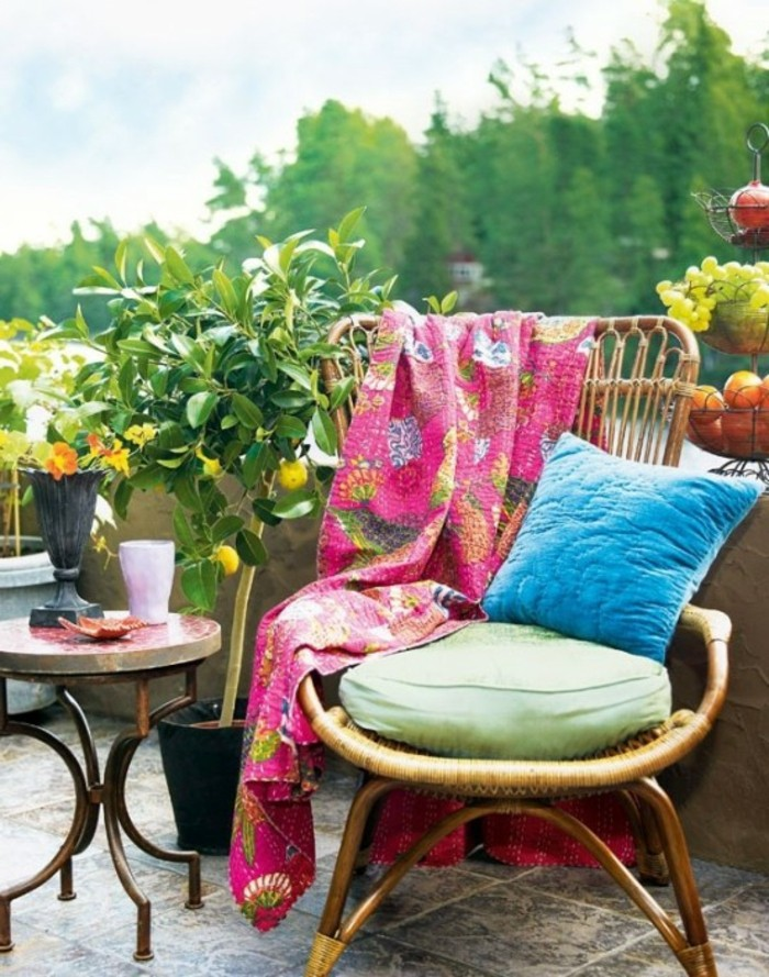 outdoor patio ideas, bamboo chair with green and blue pillows, and pink blanket with floral pattern, near small round table, and potted lemon tree with ripe fruit