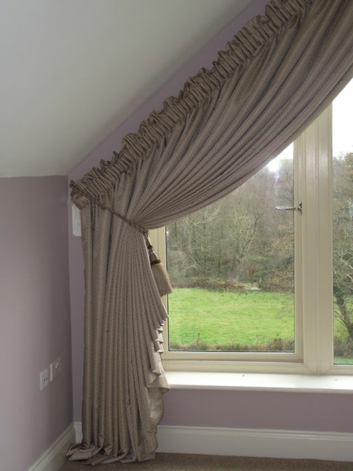 living room curtains ideas, close up of attic window, with pale brown curtain, tied with tasseled rope, pale pink wall and white ceiling
