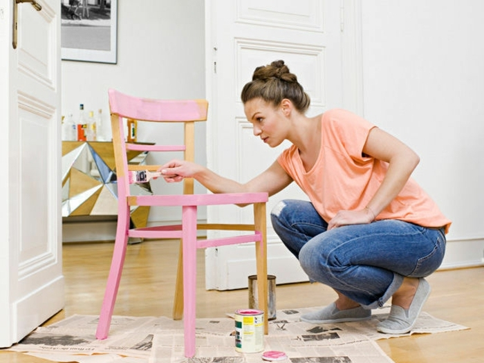 easy arts and crafts, brunette woman in jeans and t-shirt, painting a chair in pale pink, furniture and newspapers