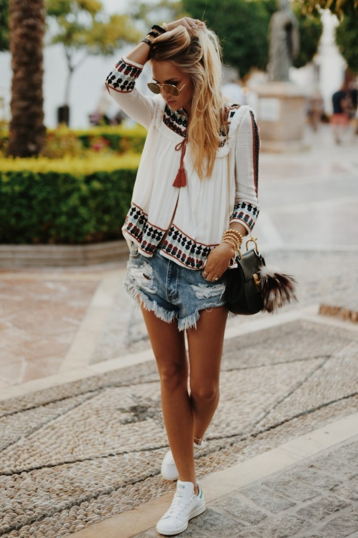 casual clothes, blonde woman with sunglasses, wearing white boho-style top, distressed and torn pale denim shorts, and white sneakers