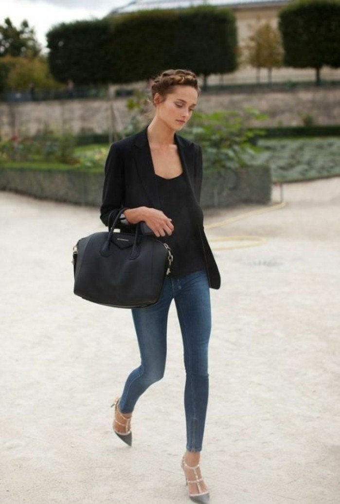 casual business attire, plain black top, and skinny blue jeans, worn with black blazer, grey strappy shoes and large black leather bag, by young brunette woman with hair done up