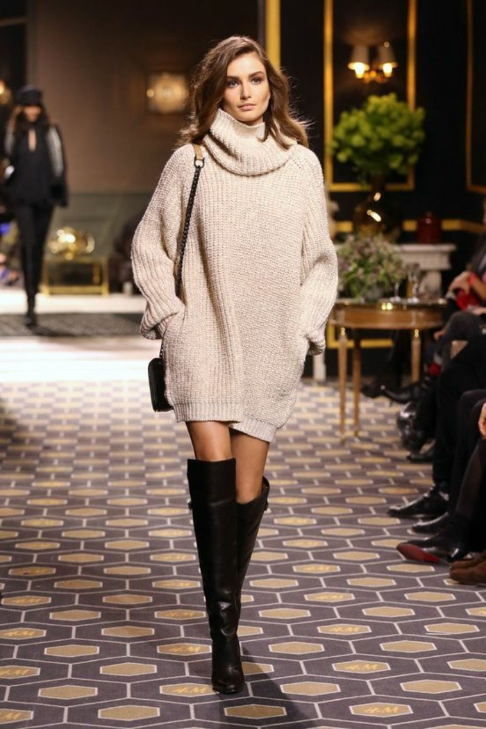 cute work outfits, oversized pale beige chunky knit turtleneck jumper dress, worn by brunette model, with dark knee-high boots, and small shoulder bag