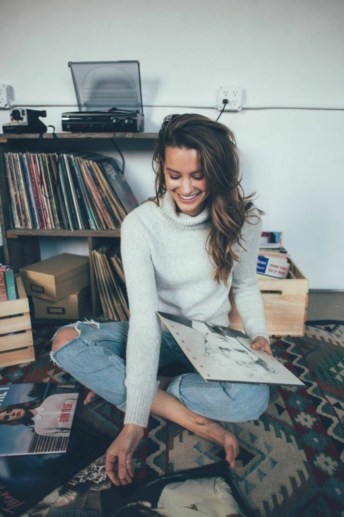 casual dress code, smiling brunette with wavy hair, wearing light grey turtleneck sweater, and pale ripped jeans with rolled legs, sitting on the floor among vinyl records
