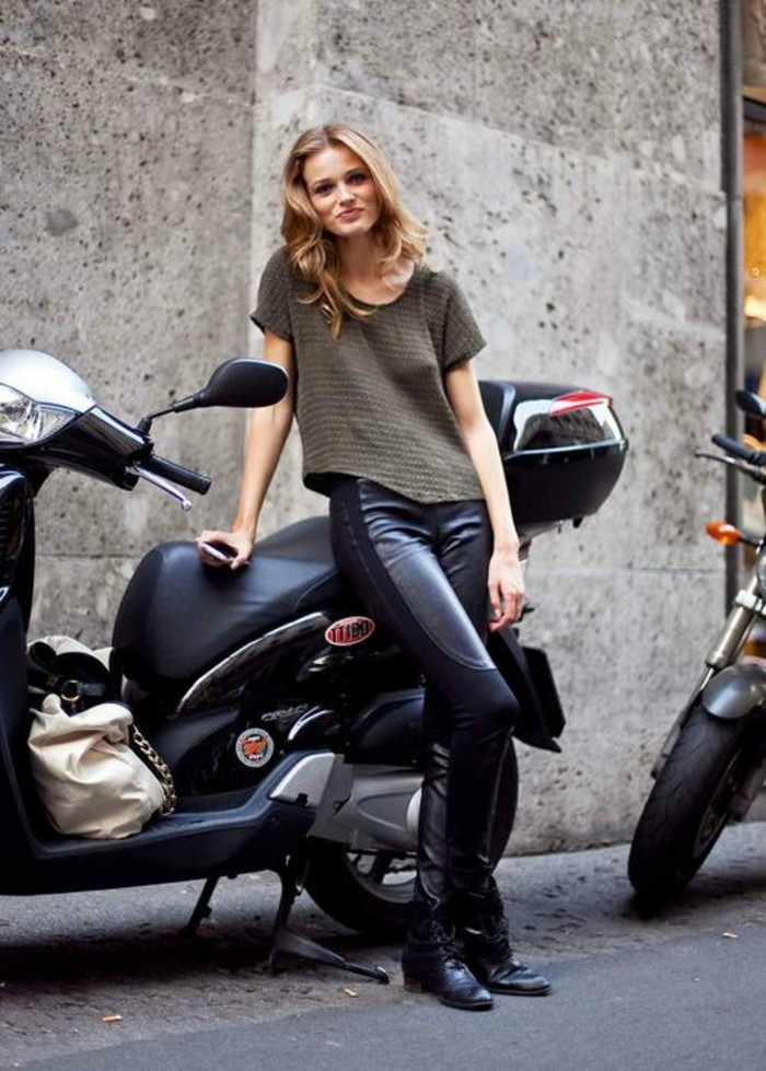 casual dress code, smiling blonde woman with wavy hair, wearing khaki striped t-shirt, and black trousers, with leather details, and leaning on black motor scooter