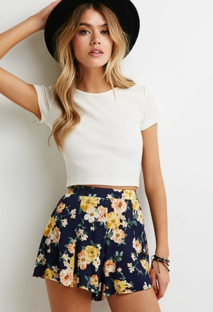 women outfits, plain white cropped t-shirt, and dark blue high-waisted shorts, with white, yellow and orange flowers, worn by blonde woman with long wavy hair, and black felt hat