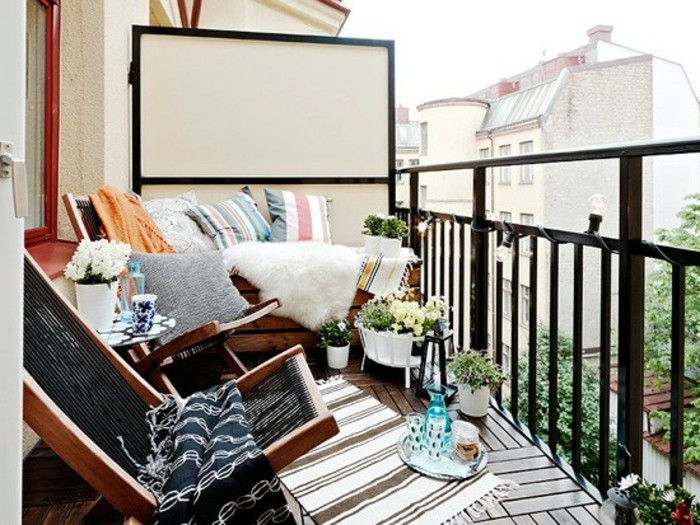 two wooden lounging chairs, a wooden settee covered in throws, pillows and a white sheep skin, front porch decorating ideas, small striped rug and potted plants
