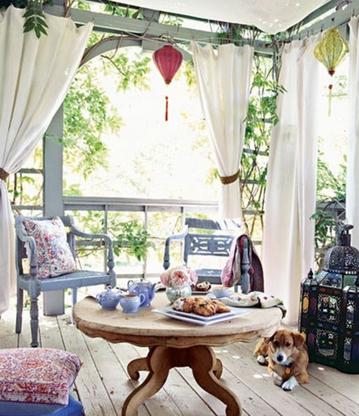 covered patio ideas, round wooden table, with tea set and pastries, two pale blue ornate chairs, covered patio ideas, white curtains and a dog