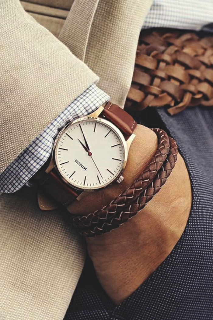 wristwatch with brown leather strap, and two woven brown leather bracelets, on the hand of a smartly-dressed businessman, business casual attire, beige blazer and chequered shirt