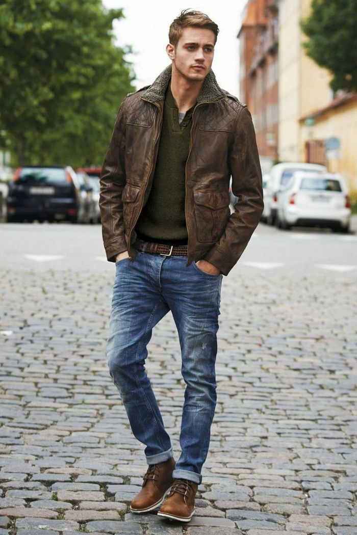 vintage-looking brown leather jacket, over khaki green jumper, casual clothes for men, combined with jeans, worn by young man, with hands in pockets