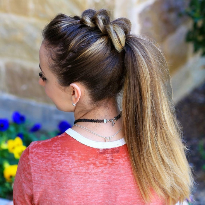 brown and blonde ombre hair, tied in high ponytail, with several braided segments, worn by woman in pink top