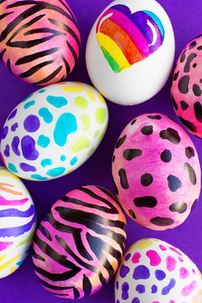 colorful eggs painted in bright neon shades, hot pink with animal print, rainbow heart on a white egg, multicolored zebra and leopard print, how to dye easter eggs, purple background